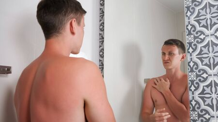 handsome guy with bare torso touches at sunburned body standing in bathroom closeup