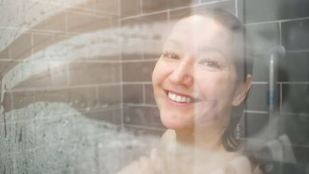 attractive lady with long wet hair smiles from shower glass door Standard-Bild