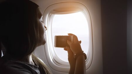 girl with long brown hair in grey t-shirt makes video on phone outside aircraft passenger cabin window close view Standard-Bild