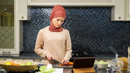 Islam woman in hijab cuts orange carrot watching halal dish recipe on Internet using laptop Standard-Bild