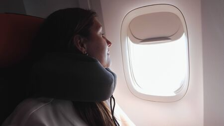 girl tourist with long brown loose hair in grey t-shirt with neckpillow looks out bright porthole in passenger cabin closeup