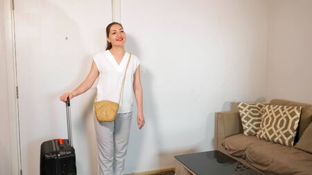 beautiful young woman in white dressing looks into handbag and leaves hotel room with large black suitcase closing door