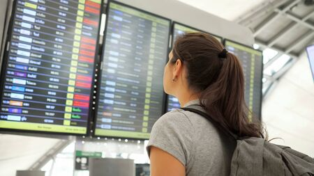 young girl with ponytail and grey backpack wearing t-shirt looks at departures schedule in airport side view