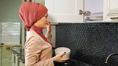 graceful woman with bright lips in hijab opens kitchen cabinet and takes clean plates for setting dinner table closeup