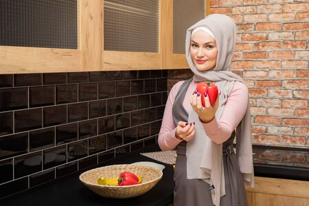 housewife in hijab holds and shows pepper in hand on the kitchen copyspace Standard-Bild