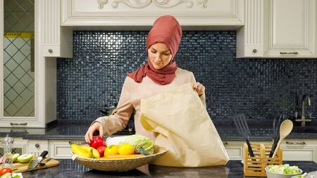 pretty Muslim woman in hijab takes out bought products from large bag for making dinner at kitchen closeup