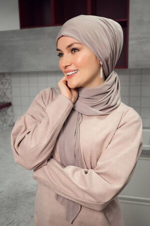 Beautiful well-groomed woman in a hijab looks away and smiles closeup