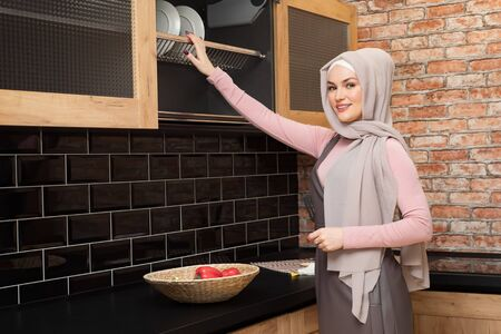 Muslim woman opens kitchen cabinet and takes clean plates on modern kitchen copyspace