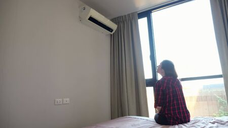 brunette turns on air conditioner with remote control sitting on bed edge at large window with bright light in hotel room Standard-Bild