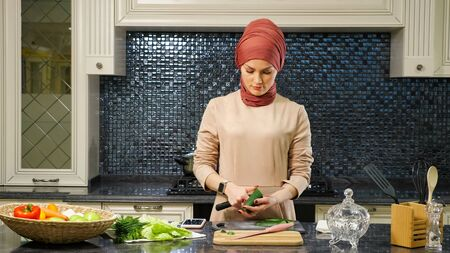 attractive housewife in hijab prepares dinner for family cutting fresh vegetables and making salad at kitchen table closeup