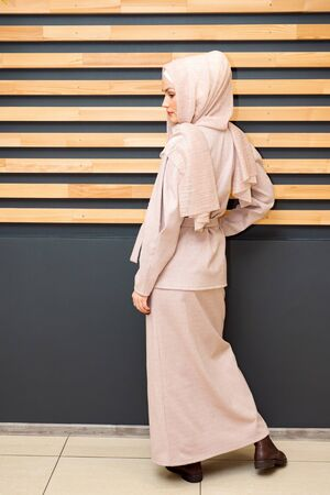 young woman in a hijab and a closed pink full-length suit back view