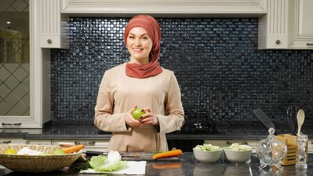cheerful woman in hijab blogs culinary show telling subscribers fruit salad recipe standing in home kitchen closeup