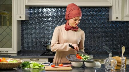 attractive housewife in hijab put cut fresh vegetables in deep plates preparing halal food for husband closeup