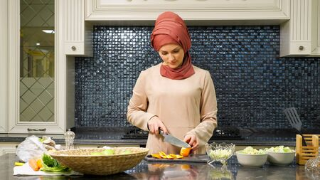 charming Islam woman in hijab makes special fruit salad cooking homemade meal for family closeup Standard-Bild