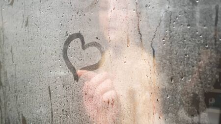 blurry naked young woman hand draws heart on bathroom glass-enclosed shower with white steam at home close view