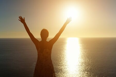 woman in summer dress silhouette stands and raises hands on ocean beach against sunset copy space