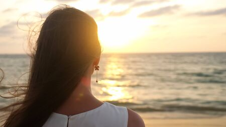 young woman with long loose hair stands on ocean beach at tropical resort in windy evening at sunset closeup