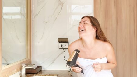 delighted young woman in towel dances and sings into modern hairdryer as microphone looking into mirror in home bathroom Stok Fotoğraf