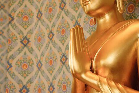Close up of hands of golden Buddha statue copyspace