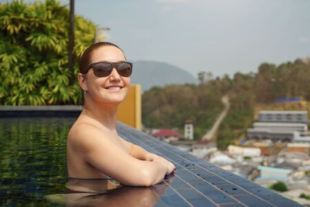 Pretty girl in black sunglasses spends time standing in swimming pool copyspace. travel concept