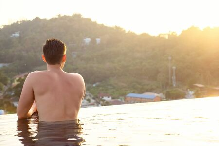 man in hotel outdoor swimming pool looking at pictorial tropical forestry hilly landscape backside view Stok Fotoğraf