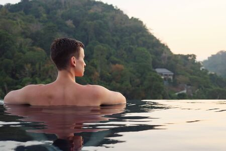 Young attractive sexy male relaxing in the swimming pool backside view, leisure and travel in warm countries Stok Fotoğraf