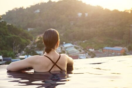 brunette looks at green forestry hills sitting in hotel swimming pool water with bright sunlight reflections backside view Stok Fotoğraf