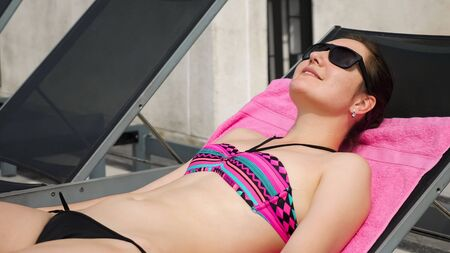 Attractive girl in sunglasses and bikini sunbathes on lounger by hotel pool closeup
