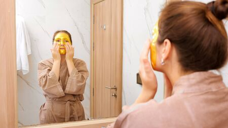 brunette woman in brown bathrobe with golden cosmetic mask does face massage near mirror in hotel bathroom close reflection