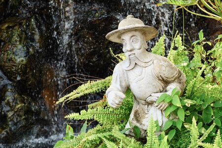 Plaster statue of a man with a beard in a hat among the fern.