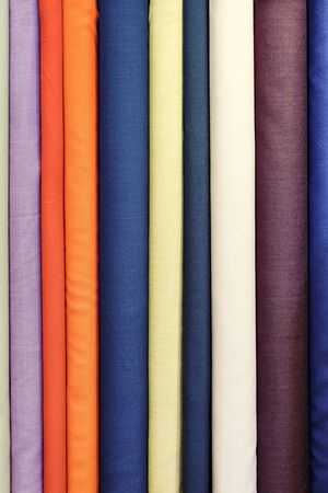Beautiful fabrics of different colors in an upright position. Bright background image.