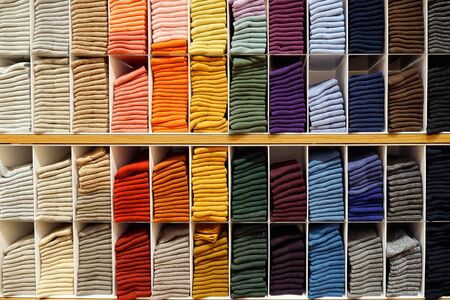 Shelves with pullovers of different plain colors folded from light to dark.