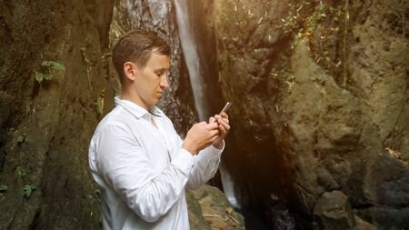 concentrated young man with short dark hair wearing white shirt holds smartphone in hand taps on screen and chats against waterfall in park closeup