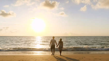 happy couple walking joining hands along beach to ocean surf against sunset at tropical resort close up