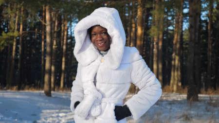 smiling African-American girl in white fur coat dresses hood in winter park closeup