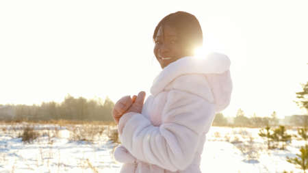African-American lady in white fur coat in snowy field at back sunlight close up Stok Fotoğraf