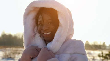 positive African-American lady in white fur hood poses smiling against empty forest in cold winter at back sunlight closeup Stok Fotoğraf