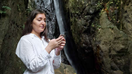 concentrated dark haired lady in headphones holds golden smartphone scrolls and reads information against tropical waterfall in reserve park close view