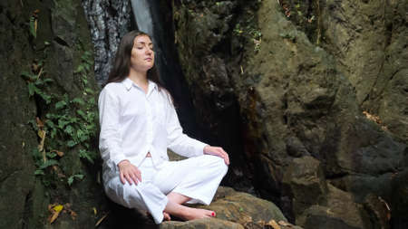 concentrated young woman with loose dark hair in special white costume sits with closed eyes in yoga lotus pose against tropical waterfall closeup