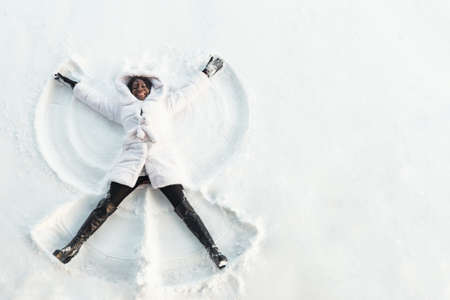 black girl in fur coat and high top boots lies on white glade and draws snow angel picture with arms and legs top view Stok Fotoğraf