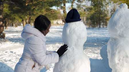 African-American girl in fur coat and black gloves makes snowman among winter nature in sunny morning