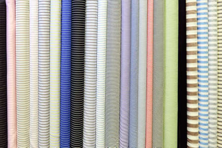 Bright background image. Rolls of different striped fabric.