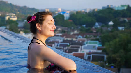 Young woman enjoys in outdoor swimming pool against blurry forestry hills and city buildings close-up copyspace