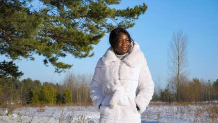 beautiful dark-skinned woman in white fur coat walks along snowy forest meadow enjoying nature on sunny day