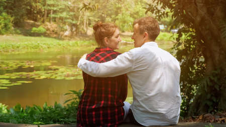 happy smiling couple hugs with love against lake on warm sunny day close up