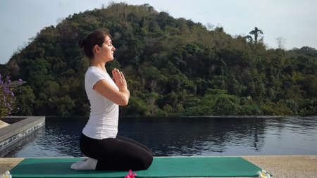 Yoga in the fresh air. Young woman meditates near the pool.