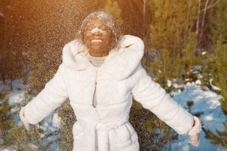 dark-skinned woman playing with snow hits her face and laughs sunlight. Stok Fotoğraf