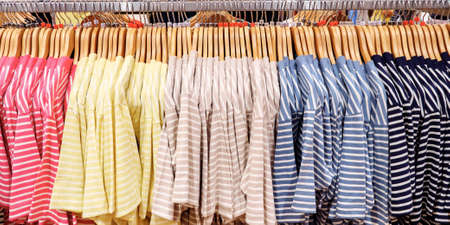 Multi-colored striped T-shirts on hangers in clothing store Stok Fotoğraf