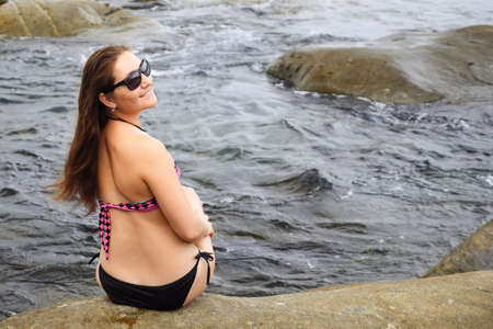 Young slim woman in stylish bikini sits on rock washed by deep blue ocean waves backside view