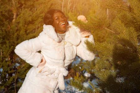 Dark-skinned woman in a white fur coat in a winter forest sunlight. Stok Fotoğraf